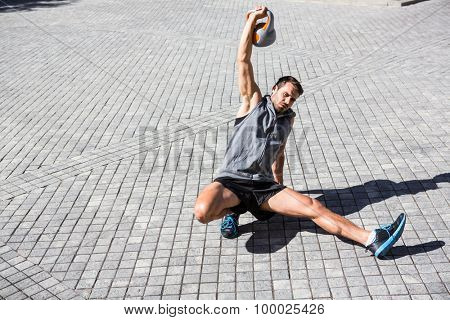 Handsome athlete exercising turkish get up in the city