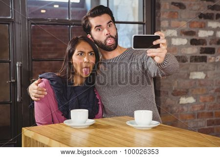 Grimacing friends taking selfies at the cafe