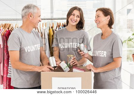 Smiling volunteers sorting donations in the office