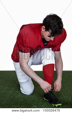 American football player tying his shoelaces on the field
