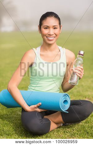 Portrait of sporty woman sitting with exercise mat and water bottle in parkland