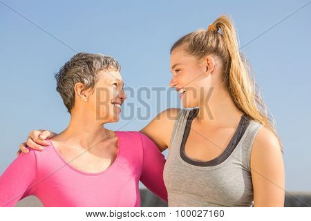 Sporty mother and daughter smiling at each other at promenade