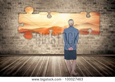 Businesswoman standing with hands behind back against sun shining over mountains