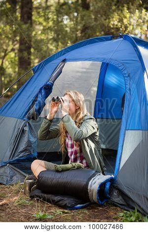 Blonde camper looking through binoculars while sitting in tent