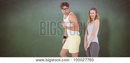 Geeky hipster couple posing in sportswear against green chalkboard
