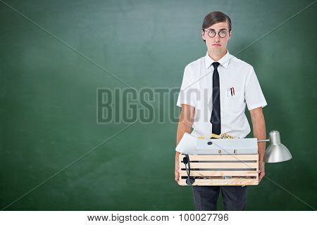Fired businessman holding box of belongings against green chalkboard