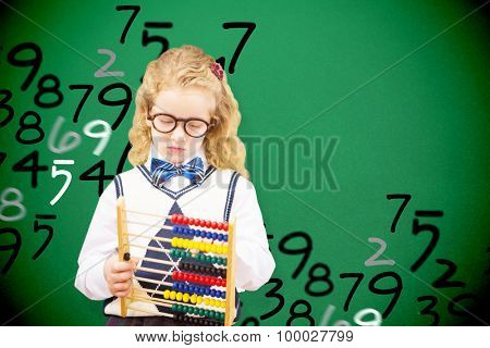 Pupil holding abacus at elementary school against green
