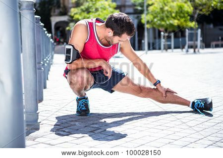 Handsome athlete doing leg stretching on the floor on a sunny day