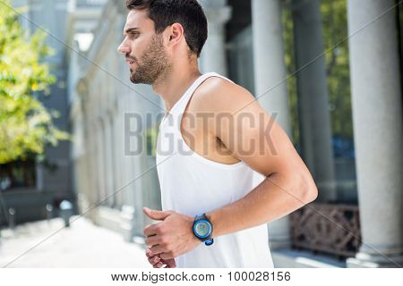 Determined handsome athlete jogging in the city