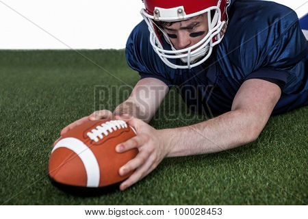 Determined american football player scoring a touchdown on the field