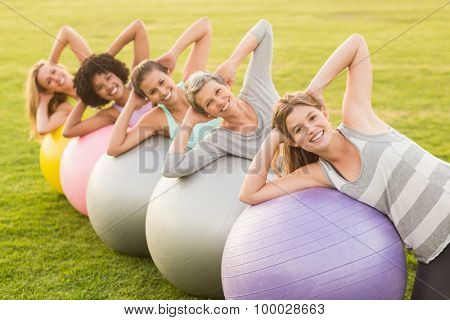 Portrait of smiling sporty women working out with exercise balls in parkland