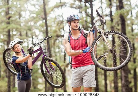 Young happy couple on bikes looking away carrying bikes in the nature