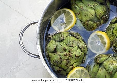 Artichokes With Lemon Slices And Water In A Stainless  Pot