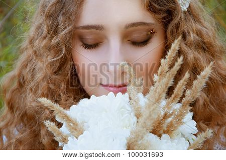 Woman with curly golden hair in the field