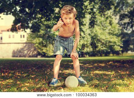 Boy In Park Ready To Kick Ball