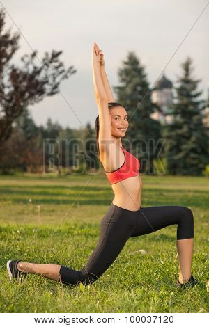 Cheerful young sport girl is exercising on grass
