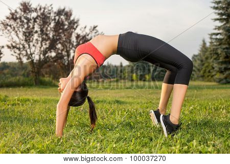 Beautiful young woman is doing exercises in park