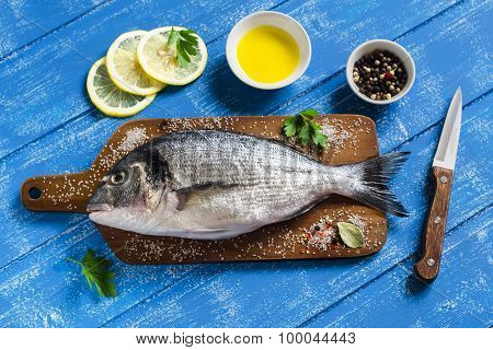 Fresh Dorado Fish With Lemon, Spices And Olive Oil On A Wooden Surface
