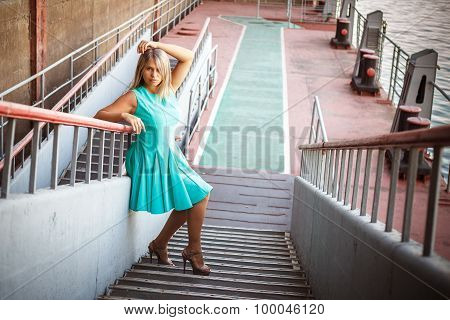 Young Beautiful Girl In A Turquoise Sundress Posing On The Steps, Outdoors