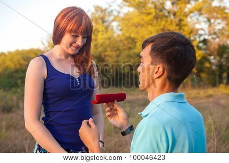 The Guy Gives The Girl A Chain In A Box In The Forest Outdoors