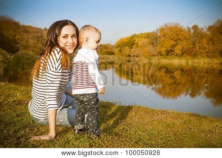 Smiling Mother And Baby On Autumn Lake