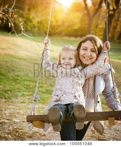 Happy Mother And Her Little Baby Swing