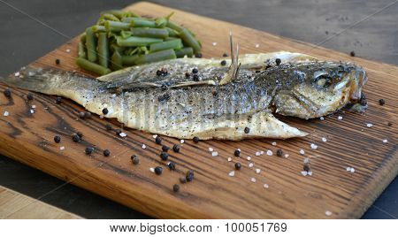 Roasted dorado fish with asparagus on wooden board