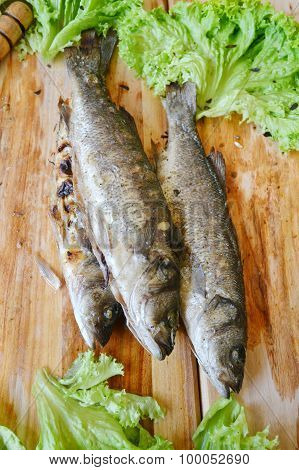 Wooden board with grilled cod fish