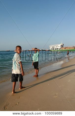 Two Boys African, Walking Along The Shoreline Sandy Beach, Zanzibar.