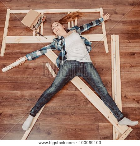Happy Woman Having Fun Assembling Furniture.