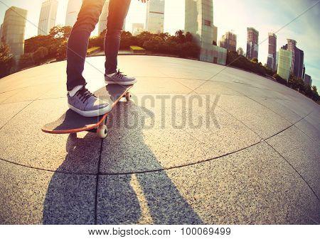 closeup skateboarder legs skateboarding at sunrise city
