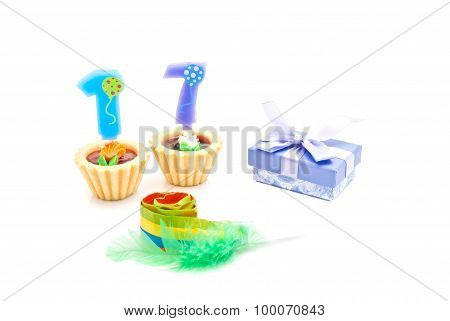 Cakes With Seventeen Years Birthday Candles, Whistle And Gift On White