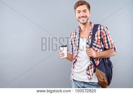 Upbeat student drinking coffee