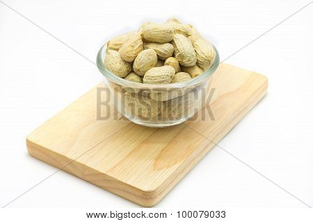 Glass bowl of peanuts on wooden board, white background