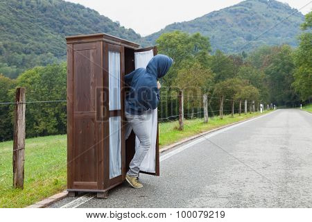 Man inside of a wooden wardrobe abandoned on a mountain road