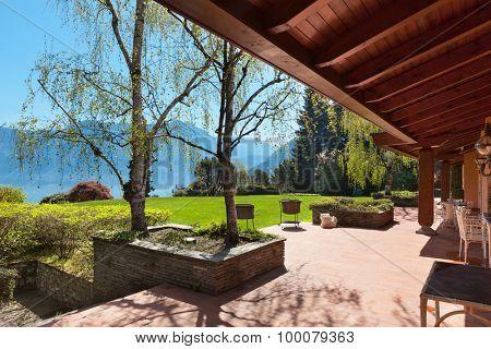 veranda of a villa with garden in a sunny spring day
