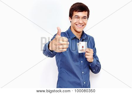 Young hispanic man wearing jeans and glasses holding two aces (clubs and hearts) in his hand and showing thumb up hand gesture with smile against white wall - gambling concept