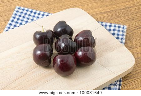 Stack Of Red Plums On A Wooden Cutting Board
