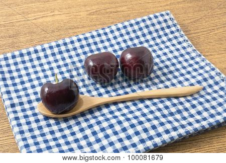Stack Of Red Plums On A Blue Checked Napkin