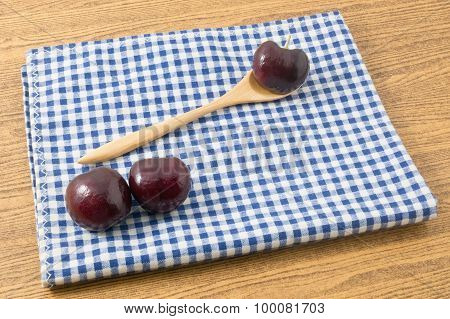 Red Ripe Plums On A Blue Checked Napkin