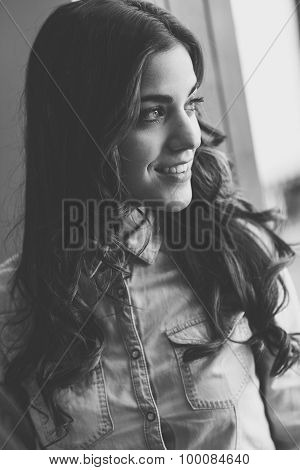 Beautiful Young Woman Looking Through The Window