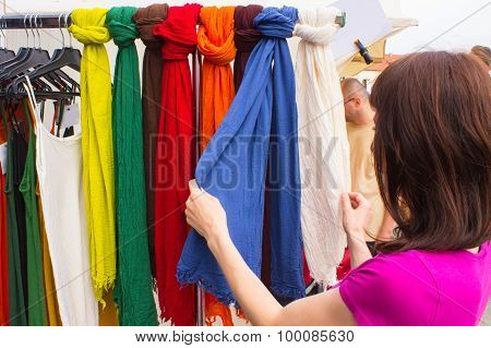 Woman Shopping Clothes On Stall At The Bazaar
