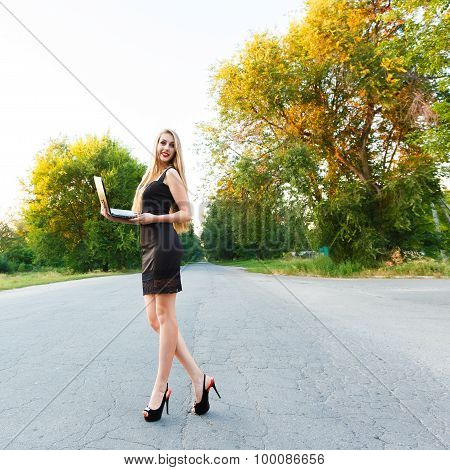 Young Beautiful Slender Woman With A Laptop On The Road