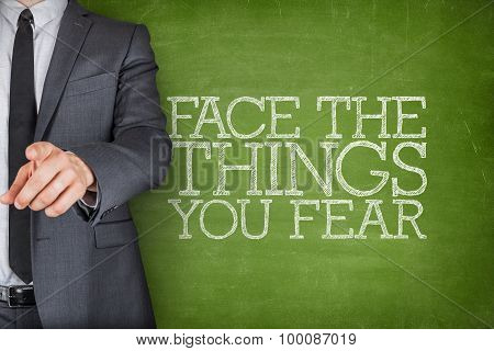 Face the things you fear on blackboard with businessman
