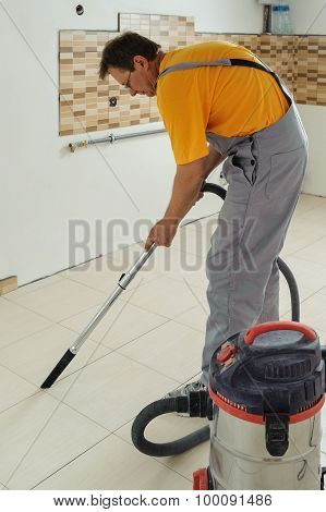 Worker Cleans Seams Between Tiles