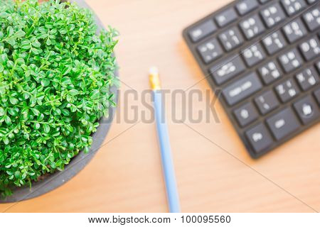 pen and keyboard placed on a wooden table with vintage style