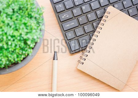 The concept composition with a black keyboard and a notebook with a pen on a wooden table beautifull