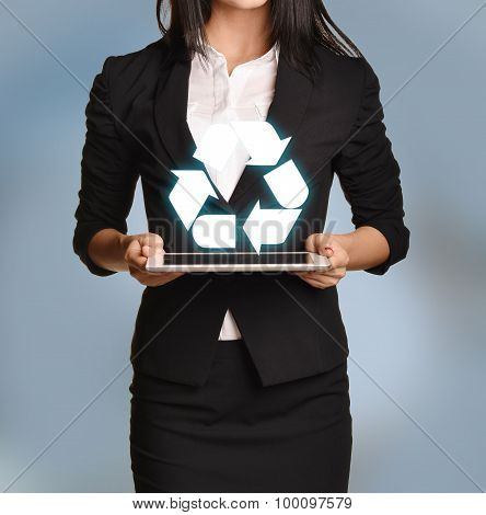 Woman is holding tablet with recycling icon