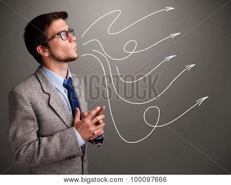 Attractive young man looking at multiple curly arrows