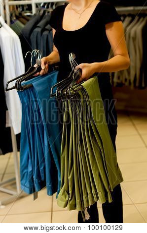 Green and blue men's trousers on hangers in female hands